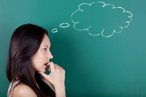 Mujer pensando con una pizarra verde detrás