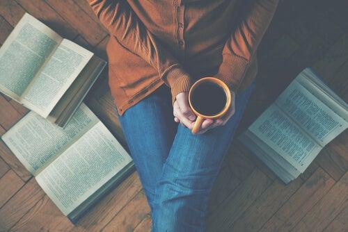 Mujer tomando café sentada en el suelo con libros