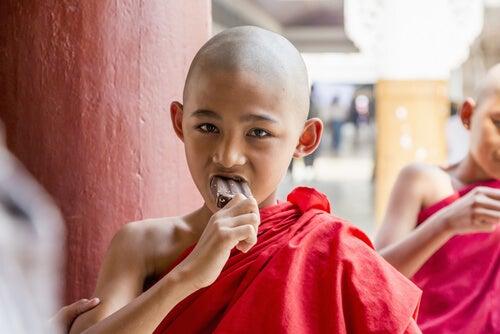 Niño budista comiendo un helado de chocolate