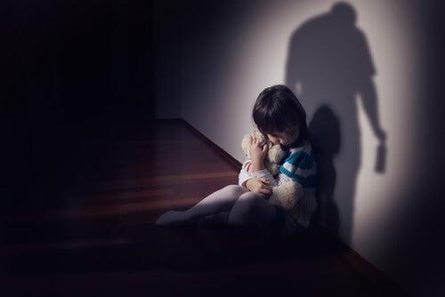 Niño con miedo al lado de la pared
