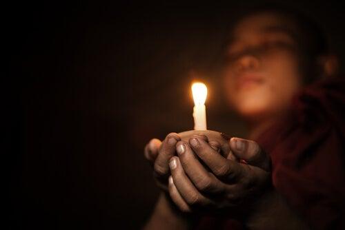 Niño budista meditando con una vela