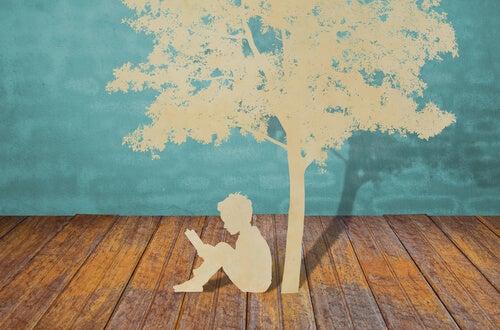Niño leyendo debajo de un árbol