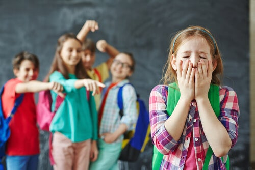 Niños riéndose de una niña