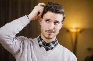 Hombre rascándose la cabeza para representar la mentira a través del lenguaje corporal