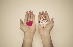 Dejar de fumar, manos con corazón y con tabaco