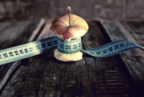 Manzana con metro alrededor representando anorexia