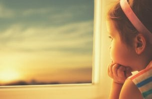 Niña mirando por una ventana con esperanza