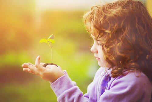 Niña mirando una planta crecer con esperanza