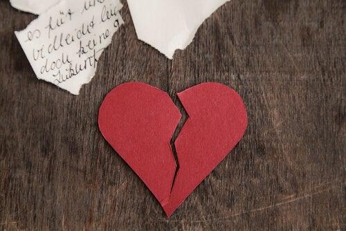 Corazón roto sobre una mesa de madera simbolizando cuando un ex rehace su vida