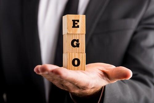 Hombre sosteniendo la palabra ego en unos cubos de madera