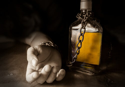 Mano encadenada a una botella de alcohol