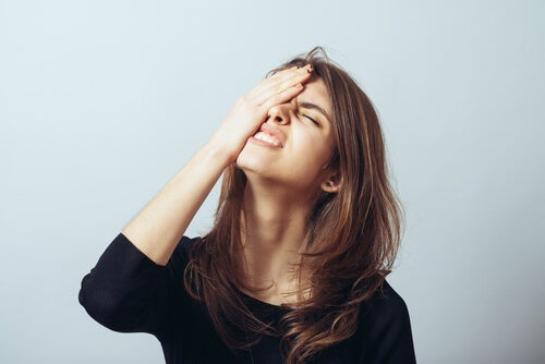 Mujer con la mano en la cabeza por su olvido