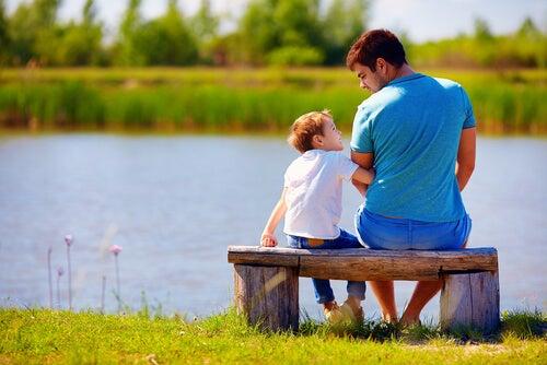 Padre hablando con su hijo sentado en un banco