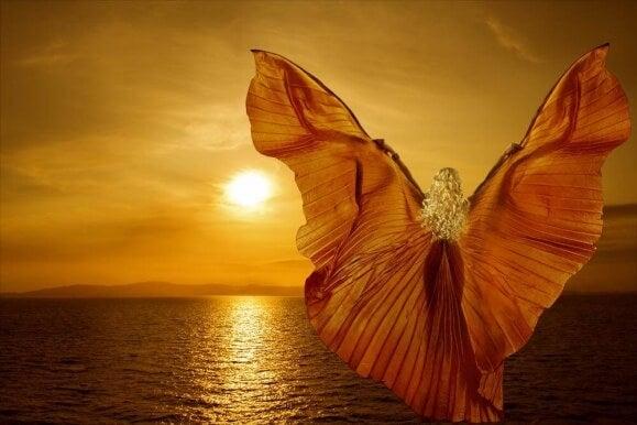 Mujer con alas soñando frente al mar