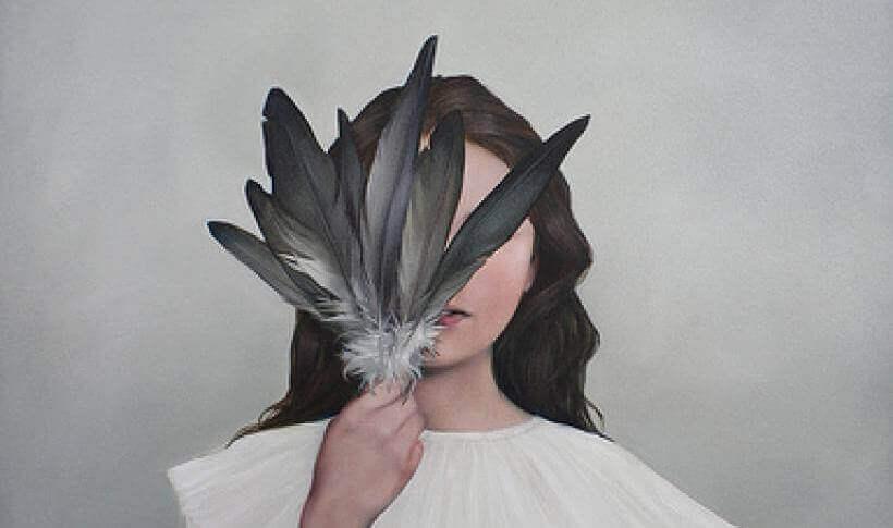 Chica tapándose la cara con unas plumas