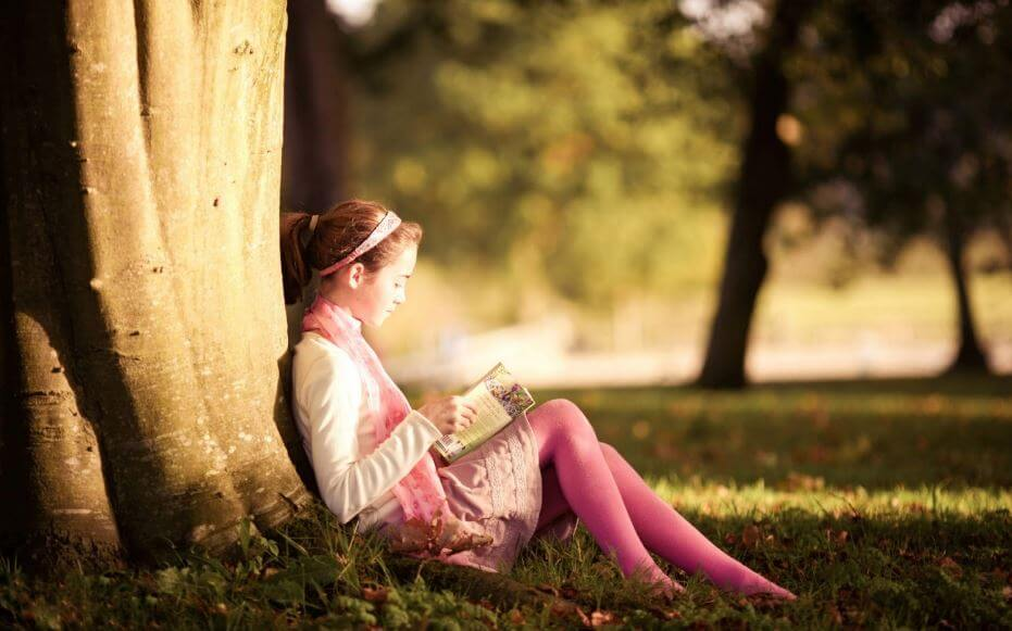Niña leyendo apoyada en un árbol