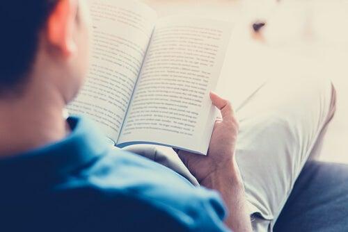 hombre leyendo libro en el sofá
