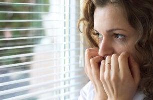 Mujer con miedo mirando por la ventana