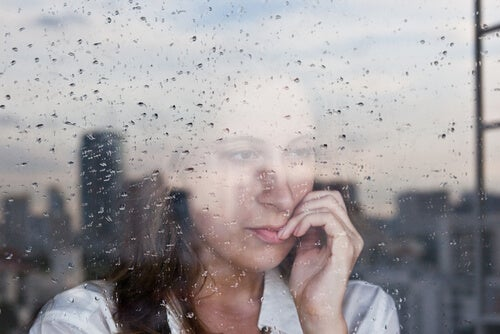 Mujer mirando por la ventana con lluvia