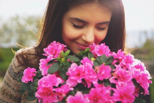 Mujer oliendo flores rosas