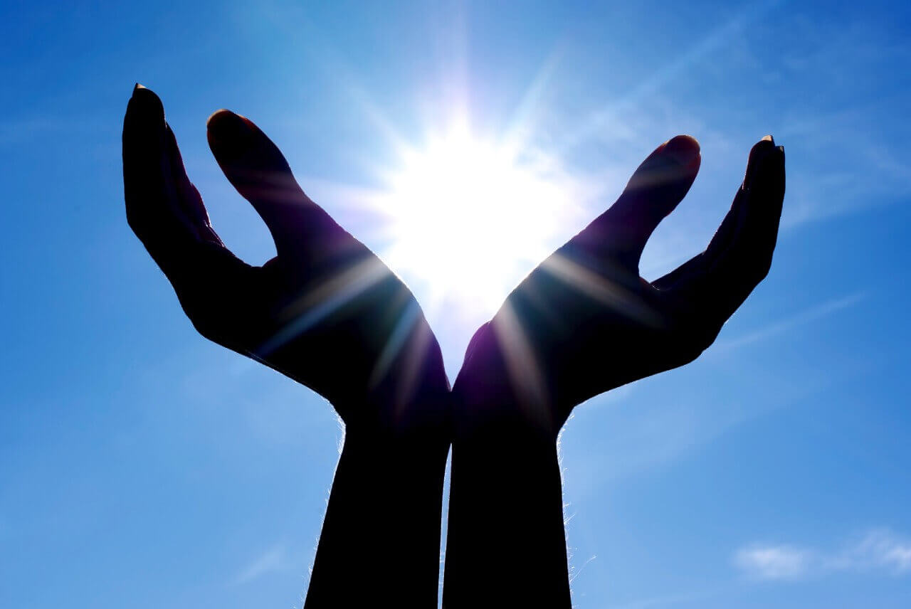 Manos abiertas al sol simbolizando la religión