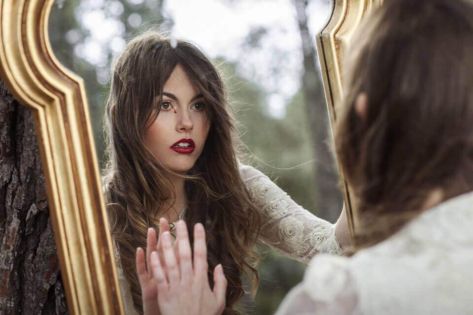 Mujer mirándose en un espejo representando las frases de La insoportable levedad del ser