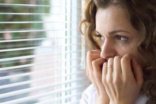 Mujer con miedo mirando por una ventana, como efecto de una alteración en el epitálamo