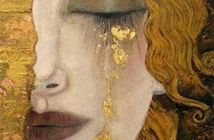 Mujer llorando con lágrimas doradas