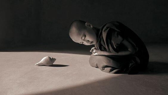 niño inclinado ante caracola