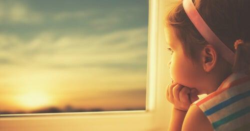Niña pequeña mirando por la ventana