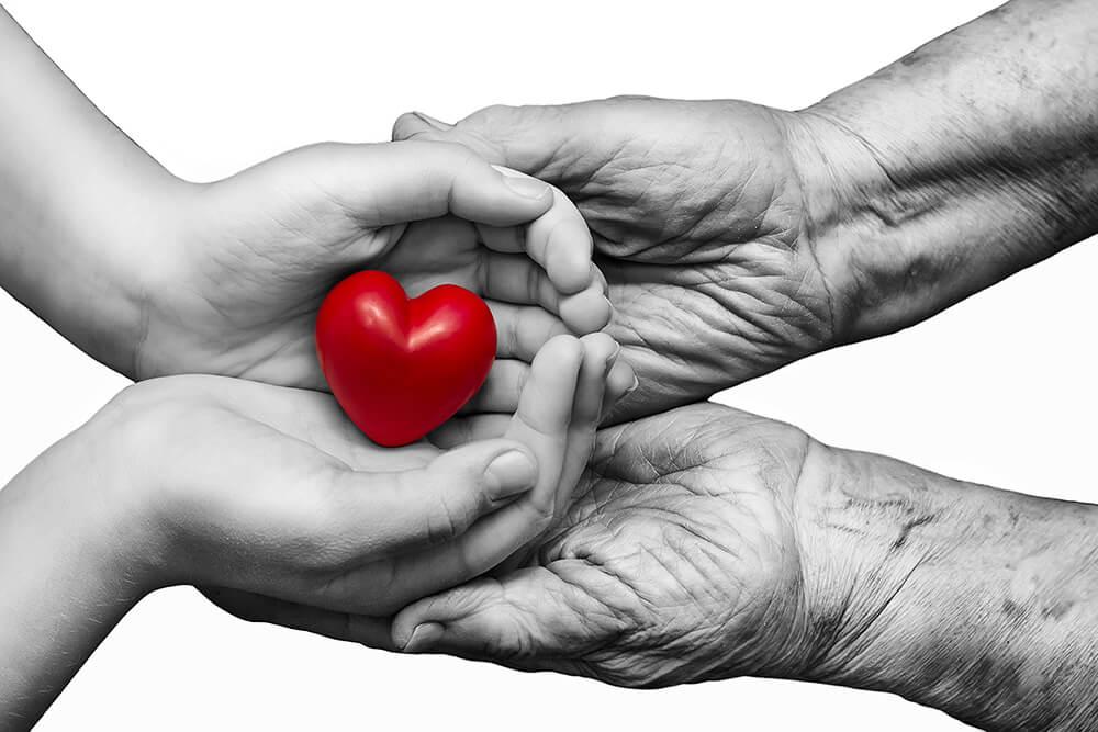 Manos diferentes edades sujetando un corazón
