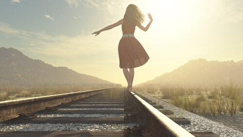 Mujer caminando por una vía mirando al futuro