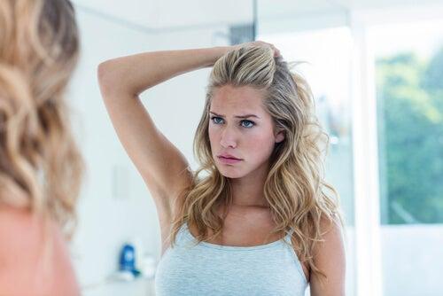 Mujer mirándose a un espejo insatisfecha
