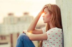 Mujer triste sentada en el suelo por su razonamiento emocional
