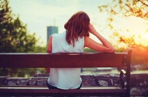 Mujer sentada en un banco sola sufriendo anuptafobia