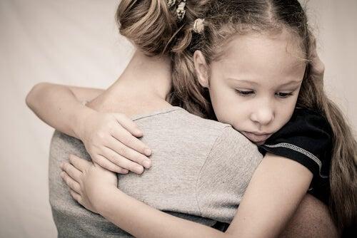 Niña temerosa abrazada a su madre