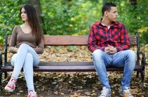 Pareja sentada en un banco enfadada