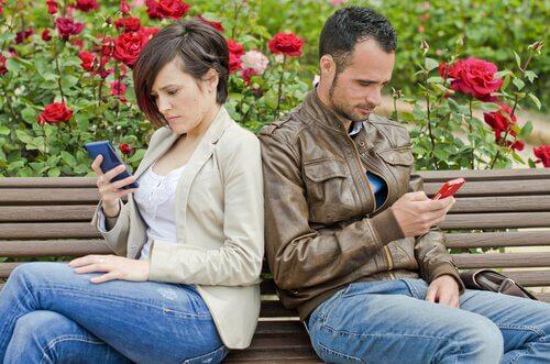 pareja de espaldas mirando móvil  simbolizando el comienzo de una relación de pareja