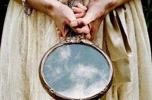 Mujer sujetando un espejo con sus manos