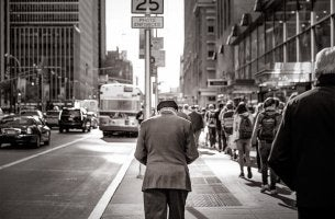 hombre mayor andando solo en la ciudad