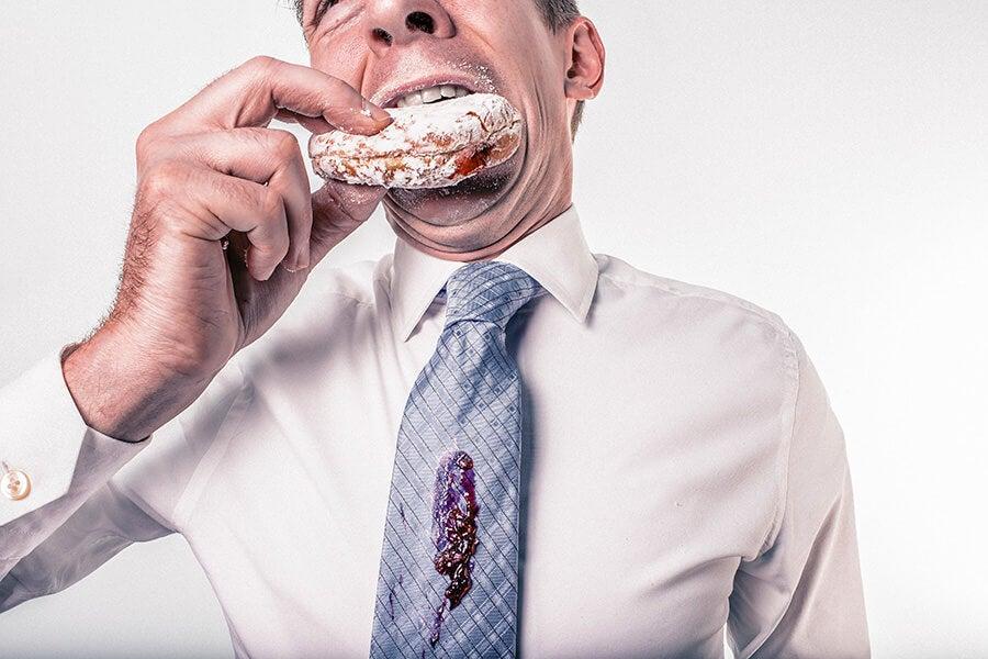hombre trajeado comiendo donut