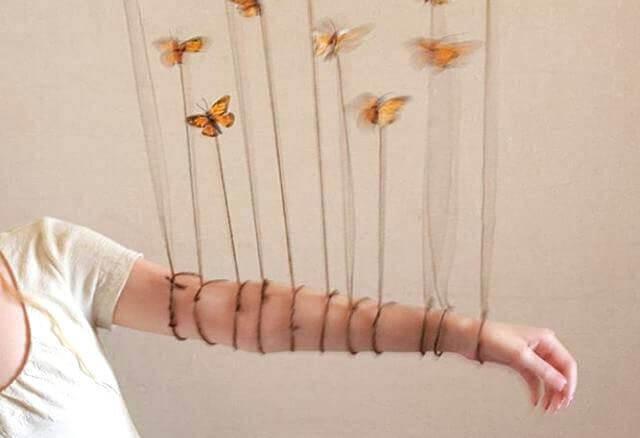 Mujer con mariposas alrededor y cuerdas sobre el brazo