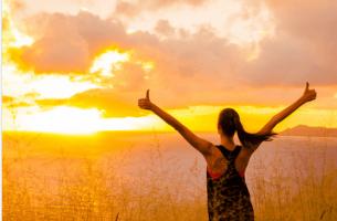 Mujer con los brazos hacia arriba simbolizando cómo desarrollar la fuerza de voluntad