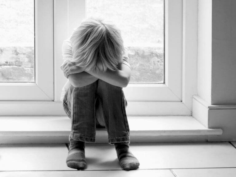Niño con padres alcohólicos llorando