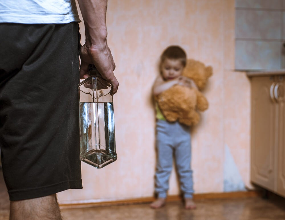 Padre alcohólico mirando a su hijo