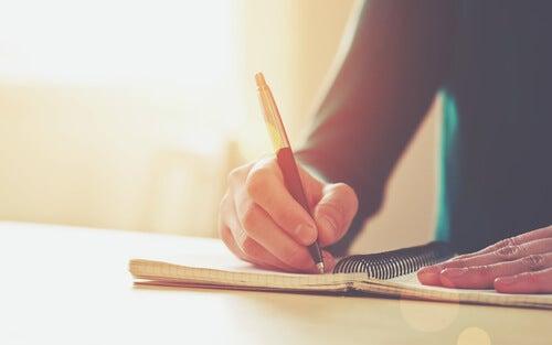 Hmbre escribiendo en una libreta