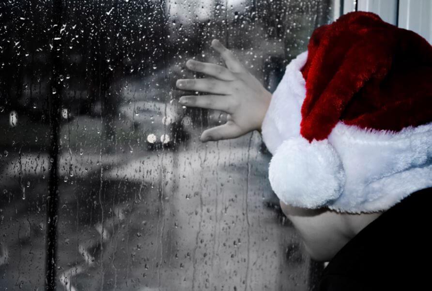 Niño con gorro de Papá Noel y fondo oscuro muestra tristeza en Navidad