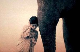 Niña con un elefante haciendo gesto de meditar