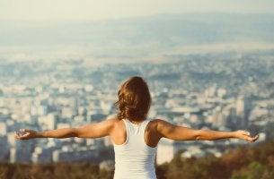 Mujer con los brazos abiertos guiándose por el principio de Pareto