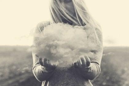 Mujer sujetando  una nube por echar de menos a alguien